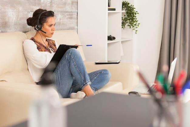 Femme en réunion d'emploi en ligne portant des écouteurs assis sur un canapé.