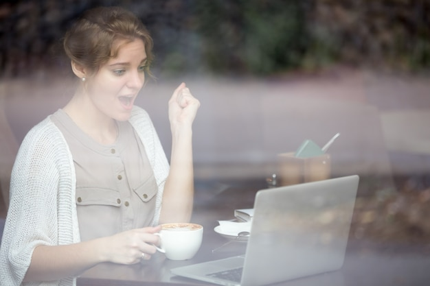 Femme réussie travailler avec son ordinateur portable
