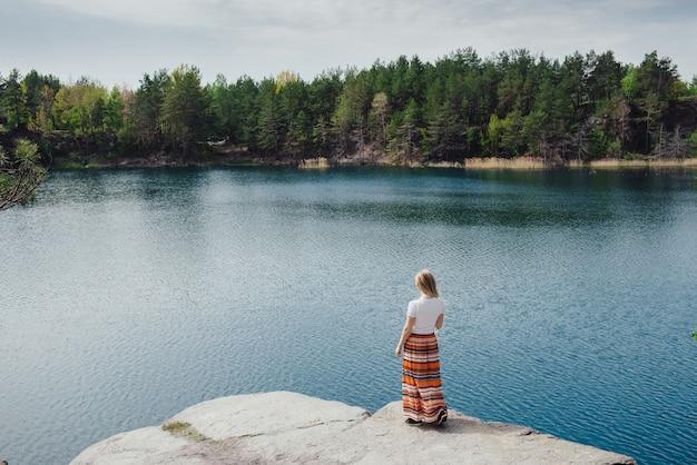 Femme réussie voyageant près du grand lac bleu, debout sur la falaise célébrant la victoire avec ses mains en jupe longue