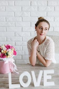 Femme rêvante avec cadeau de fleur. notion d'amour. boxe bouquet de roses colorées dans une boîte rose en forme de cylindre. beau et sensuel cadeau pour le 8 mars, saint valentin