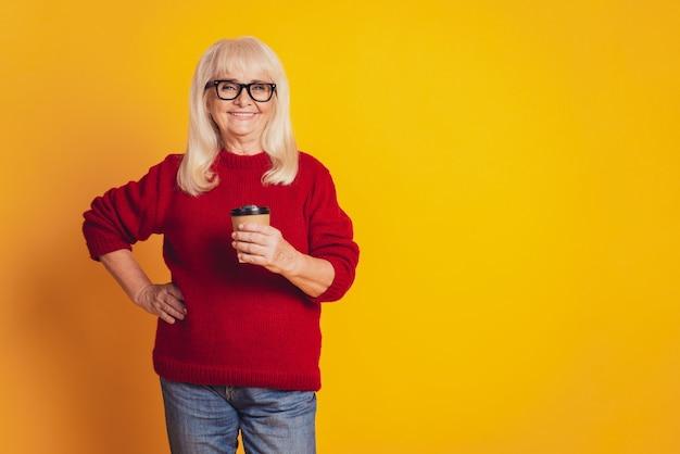 Femme de rêve détient une tasse de café jetable bénéficie d'une pause isolée sur fond jaune