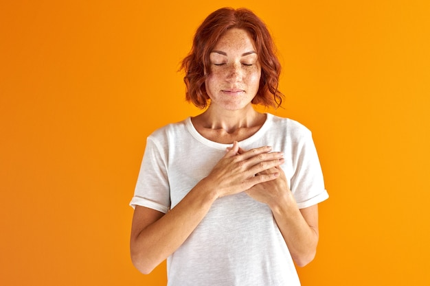 Femme rêve les yeux fermés, main dans la main sur la poitrine isolée en studio sur fond orange