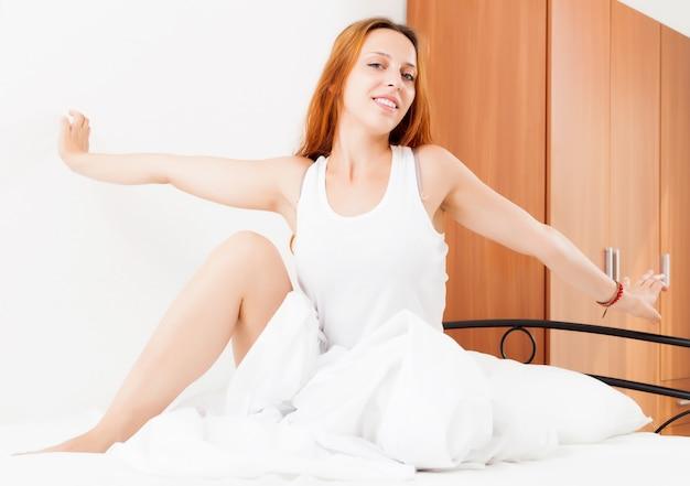 Femme réveillée au lit à la maison