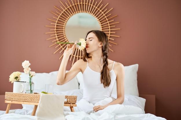 Femme rêveuse assise sur le lit et reniflant une fleur