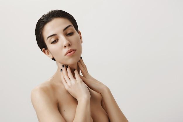 Femme rêveuse féminine debout nue dans la douche, appliquer le produit de routine de soin de la peau