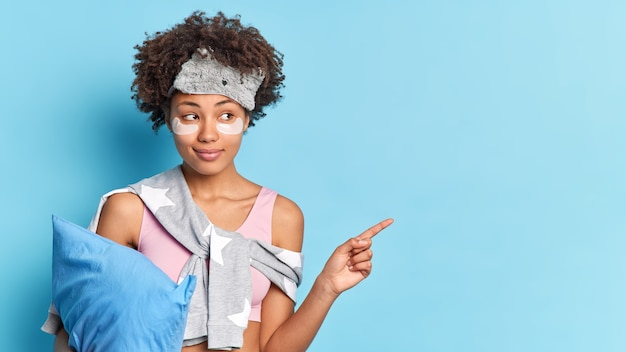 Une femme rêveuse à la peau sombre et aux cheveux bouclés applique des tampons de collagène sous les yeux pour réduire les poches après avoir dormi