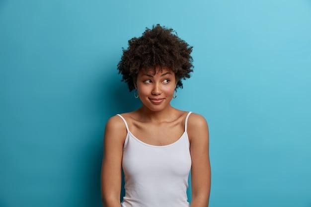 Femme rêveuse à la peau sombre positive avec des cheveux afro regarde de côté, a un sourire agréable sur le visage, vêtue d'un gilet décontracté, remarque quelque chose d'agréable, pose