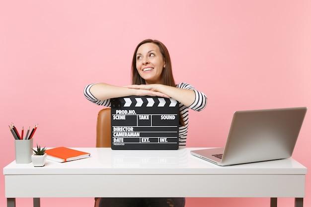 Femme rêveuse regardant s'appuyer sur un film noir classique faisant un clap et travaillant sur un projet tout en étant assise au bureau avec un ordinateur portable isolé sur fond rose. carrière commerciale de réussite. espace de copie.