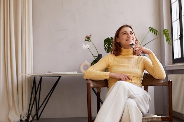 Femme rêveuse avec smartphone sur chaise à la maison
