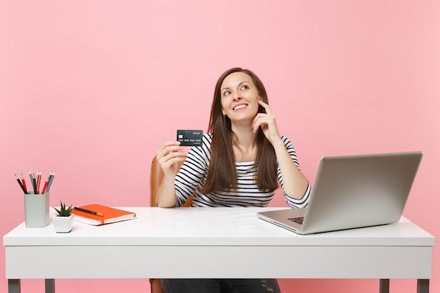 Femme rêveuse tenant une carte de crédit en levant en pensant à comment dépenser de l'argent tout en travaillant assis au bureau avec un ordinateur portable isolé sur fond rose pastel. concept de carrière d'entreprise de réalisation. espace de copie.