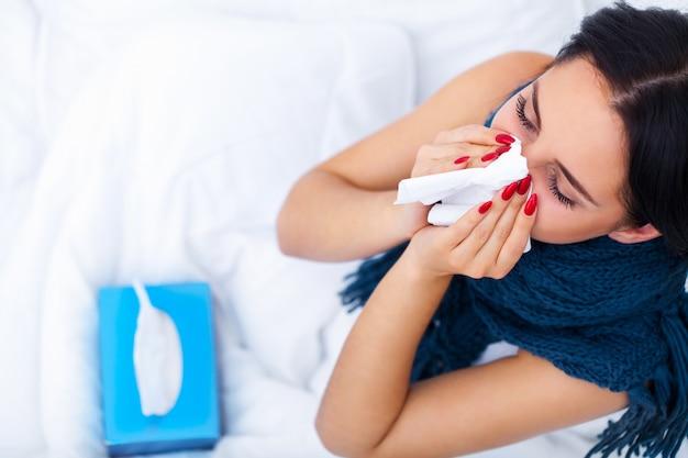 Femme avec un rhume sur le lit sous la couverture