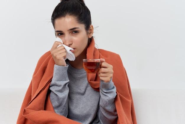 Femme avec un rhume prenant une couverture avec une couverture à la maison pour traiter des problèmes de santé