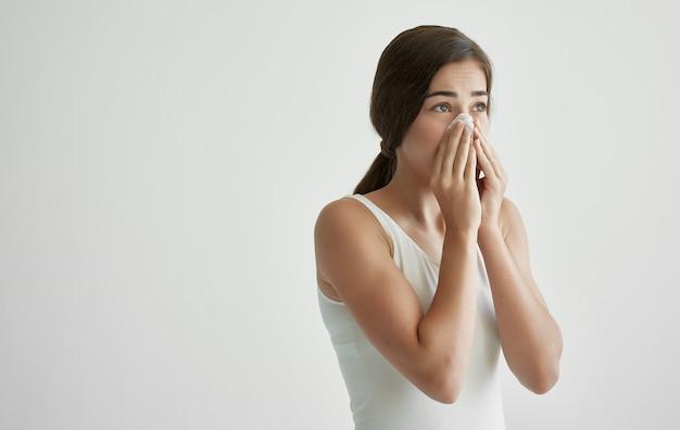 Une femme avec un rhume s'essuie le nez avec un mouchoir des problèmes de santé contre la grippe
