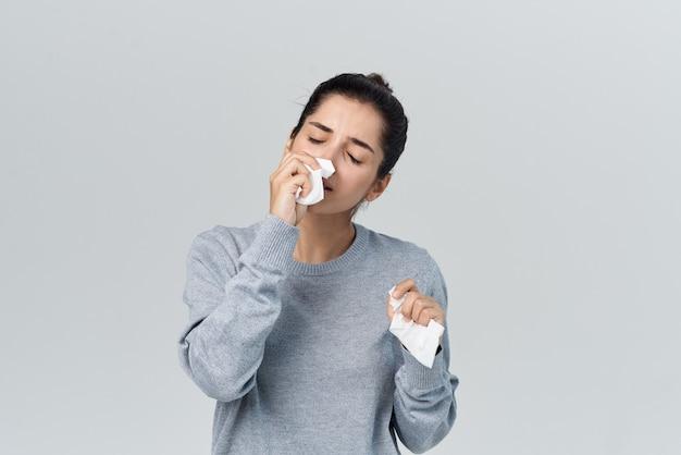 Une femme avec un rhume s'essuie le visage avec une infection allergique au mouchoir