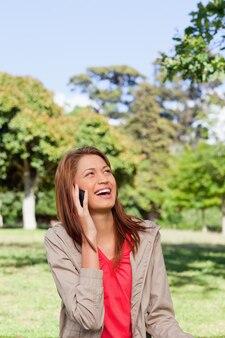 Femme riant au téléphone tout en regardant vers le soleil