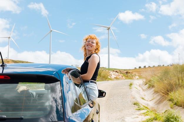 Femme riant et regardant la caméra par la fenêtre de la voiture