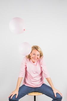 Femme riante âgée en chemisier rose sur un tabouret près des ballons