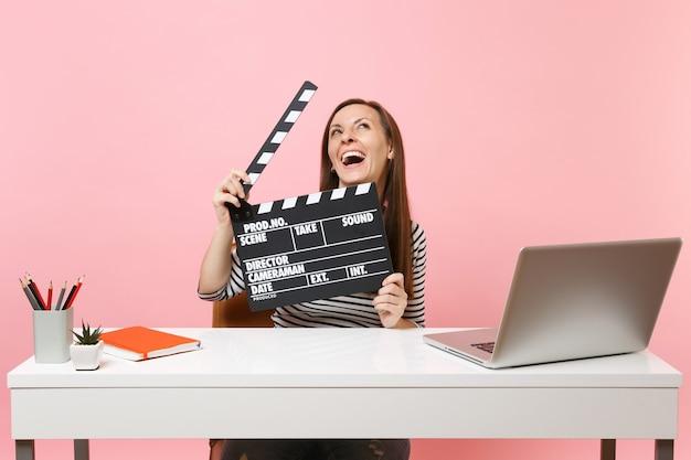 Femme riante tenant un film noir classique faisant un clap, travaillant sur un projet tout en étant assise au bureau avec un ordinateur portable isolé sur fond rose pastel. concept de carrière d'entreprise de réalisation. espace de copie.