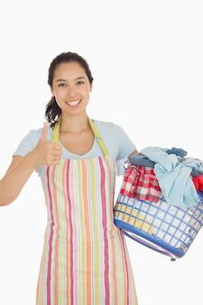 Femme riante tenant un panier à linge rempli de vêtements sales