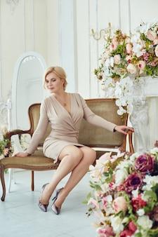 Femme riche réussie pose à la maison. jeune retraité, femme d'affaires