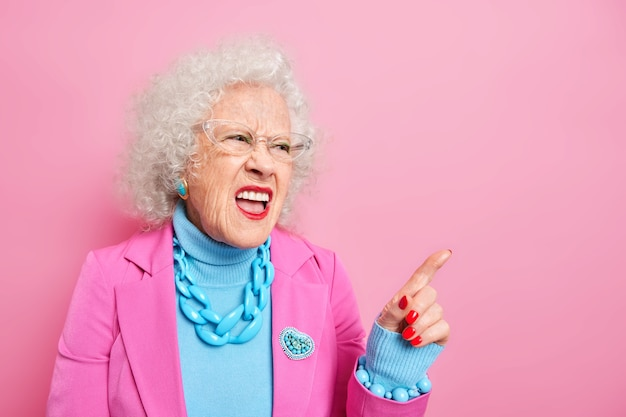 Une femme ridée et insatisfaite aux cheveux gris bouclés se tient bien habillée se plaint des prix élevés directement sur l'espace de copie
