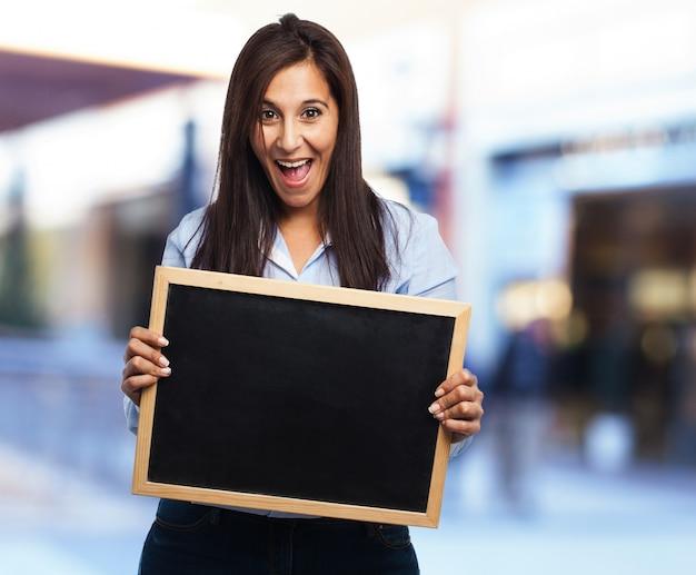 Femme rire avec la bouche ouverte tenant un tableau noir