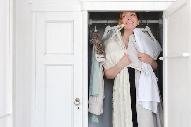 Femme rit en choisissant des vêtements dans le placard