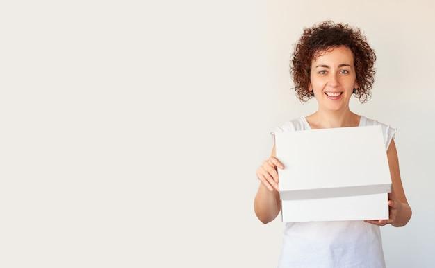 Femme rit en ouvrant une boîte sur un fond blanc isolé