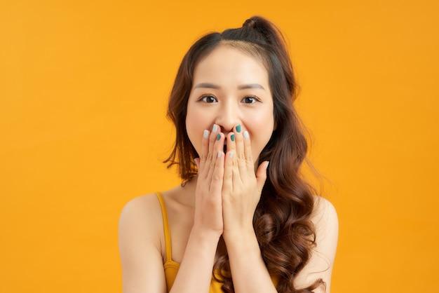 Une femme rit en se couvrant la bouche avec la main