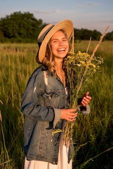 La femme rit et tient un bouquet de fleurs sauvages