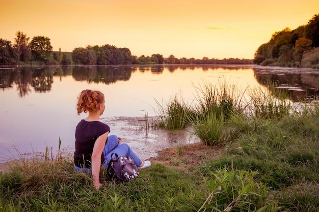 Femme sur la rive du fleuve admire la nature au coucher du soleil