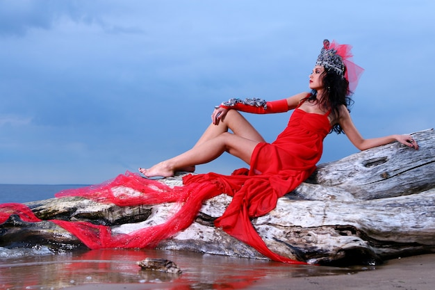 Femme en robe avant-gardiste rouge à la plage