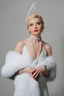 Femme en robe blanche avec bretelles et longue étole en fourrure
