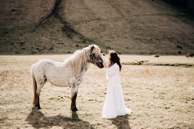 Femme en robe blanche caresse un cheval blanc au visage. islande