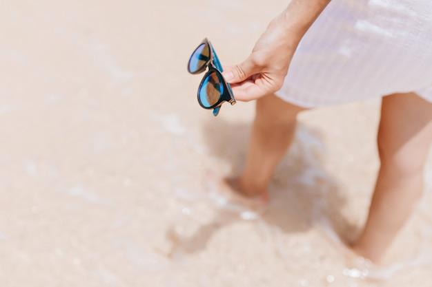 Femme en robe blanche debout dans l'eau au resort. photo d'un modèle féminin bronzé tenant des lunettes de soleil à la main.