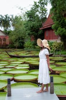 Femme en robe blanche debout sur le pont au-dessus de la piscine avec une grande feuille de lotus victoria verte