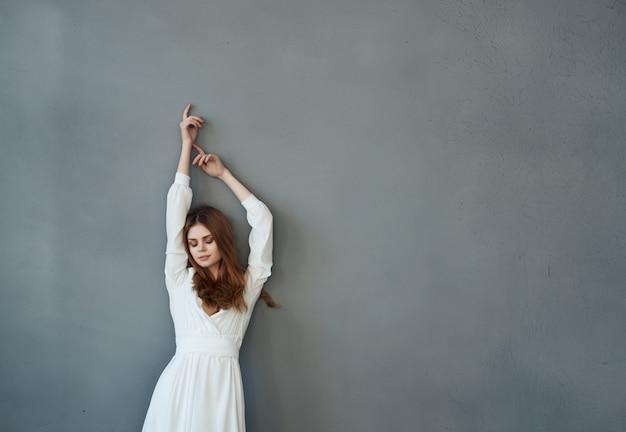 Femme en robe blanche fashion glamour et luxe posant