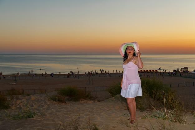 Femme en robe blanche sur fond de mer au coucher du soleil. photo horizontale