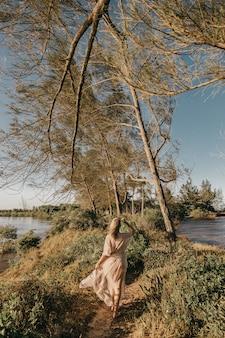 Femme en robe blanche marchant pieds nus dans une petite zone herbeuse entourée d'eau