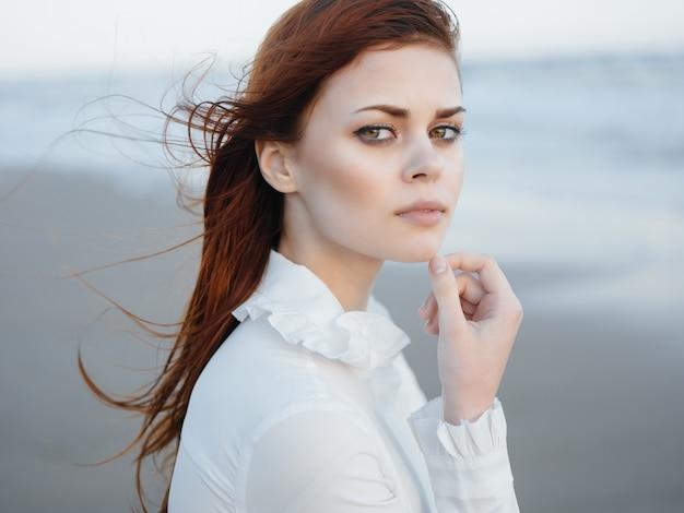 Une femme en robe blanche marche le long du luxe de la liberté au bord de l'océan