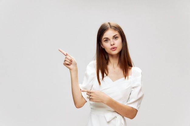 Une femme en robe blanche montre ses doigts sur le côté vue recadrée d'un fond clair