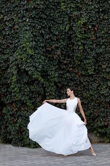 Femme en robe blanche sur mur de lierre vert