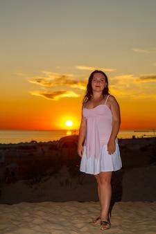 Femme en robe blanche sur la plage sur fond de mer au coucher du soleil.