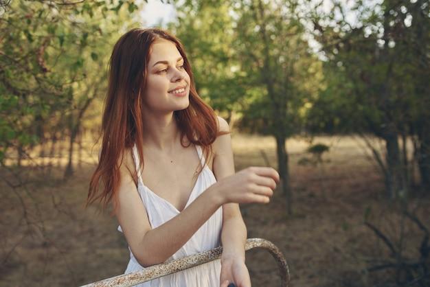 Femme en robe blanche en promenade nature arbres champ