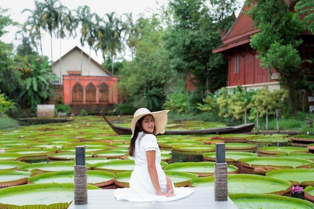 Femme en robe blanche s'asseoir sur le pont au-dessus de la piscine avec une grande feuille de lotus victoria verte
