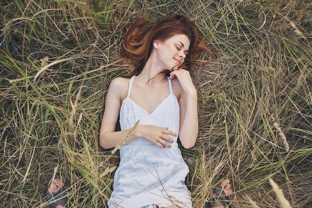 Femme en robe blanche se trouve sur le repos de la nature de l'herbe