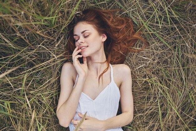 Femme en robe blanche se trouve sur le reste de la nature de l'herbe. photo de haute qualité