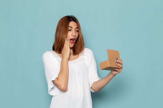 Femme en robe blanche surprise après avoir ouvert la petite boîte