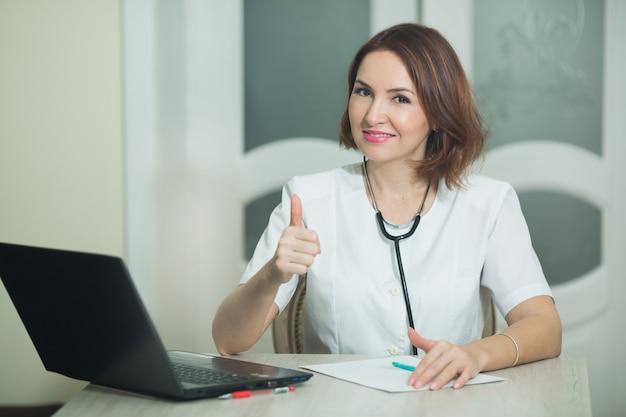 Femme en robe blanche à table avec ordinateur portable avec geste de la main