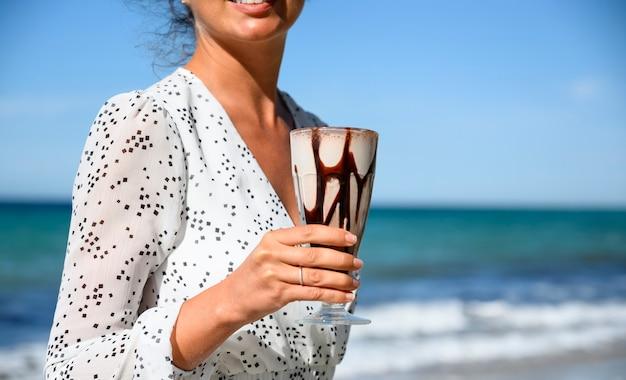 Femme en robe blanche tenant un café latte à la mer en grèce